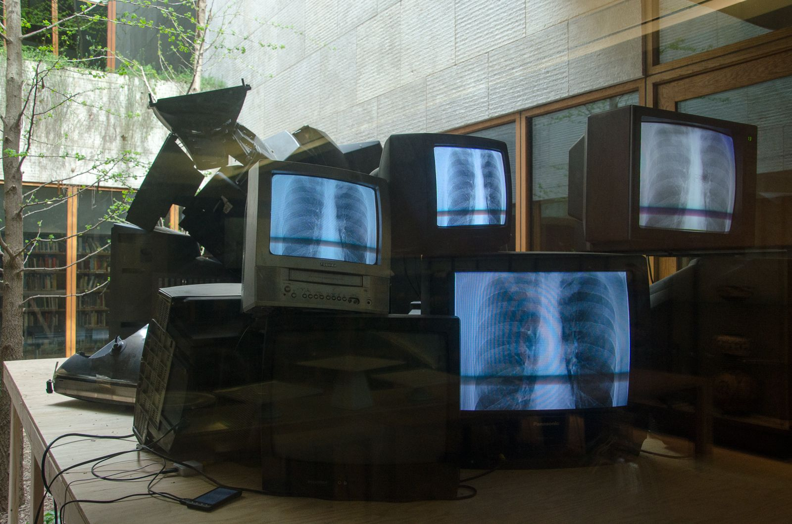 WILMER WILSON IV  a long pane beat in  2017, cords, cellphones, CRT televisions with X-ray photograph, dimensions variable. Installation view: The Barnes Foundation