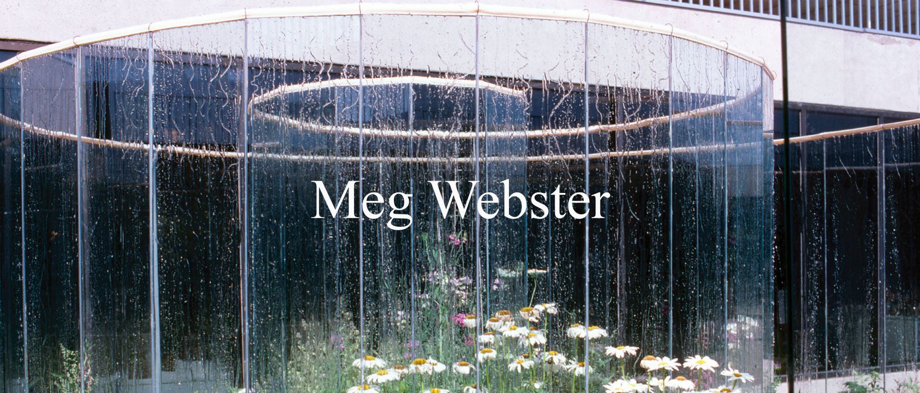 Installation view of Meg Webster's glass spiral, surrounded by growing plants and flowers.
