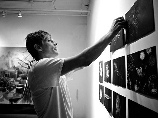 an artist hanging works on paper on his studio wall
