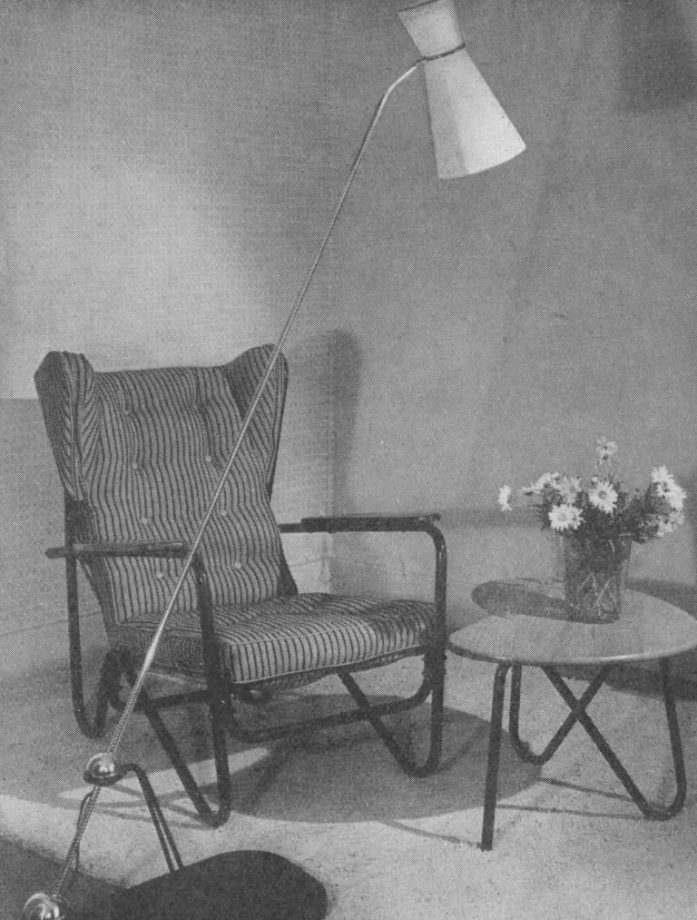 Black and white archival image of the Prefacto chair by Pierre Guariche, presented with a floor lamp and side table, c. 1950