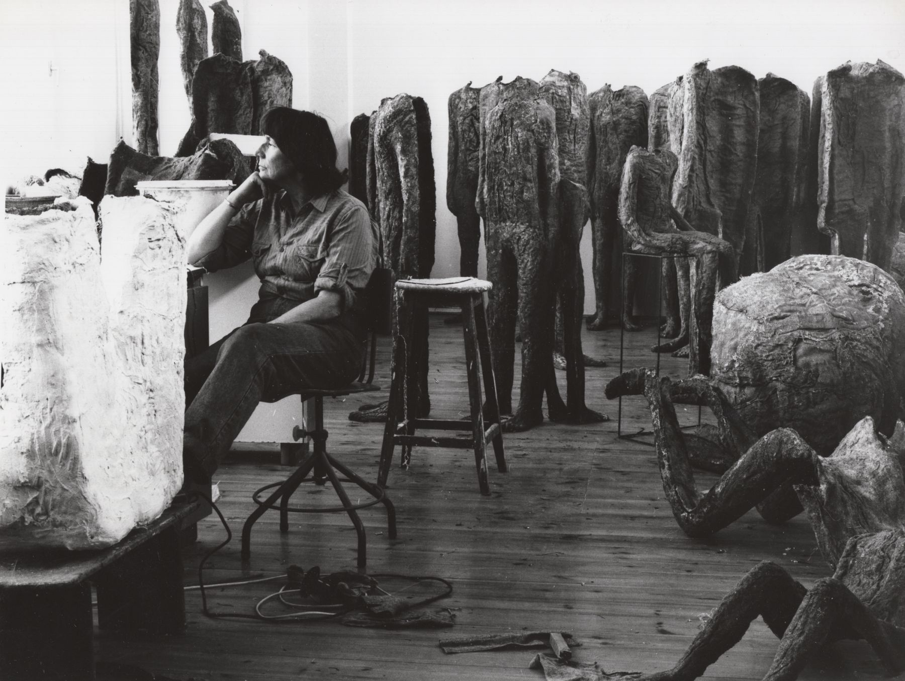 Black and white photographic portrait of Magdalena Abakanowicz in her studio surrounded by sculptures