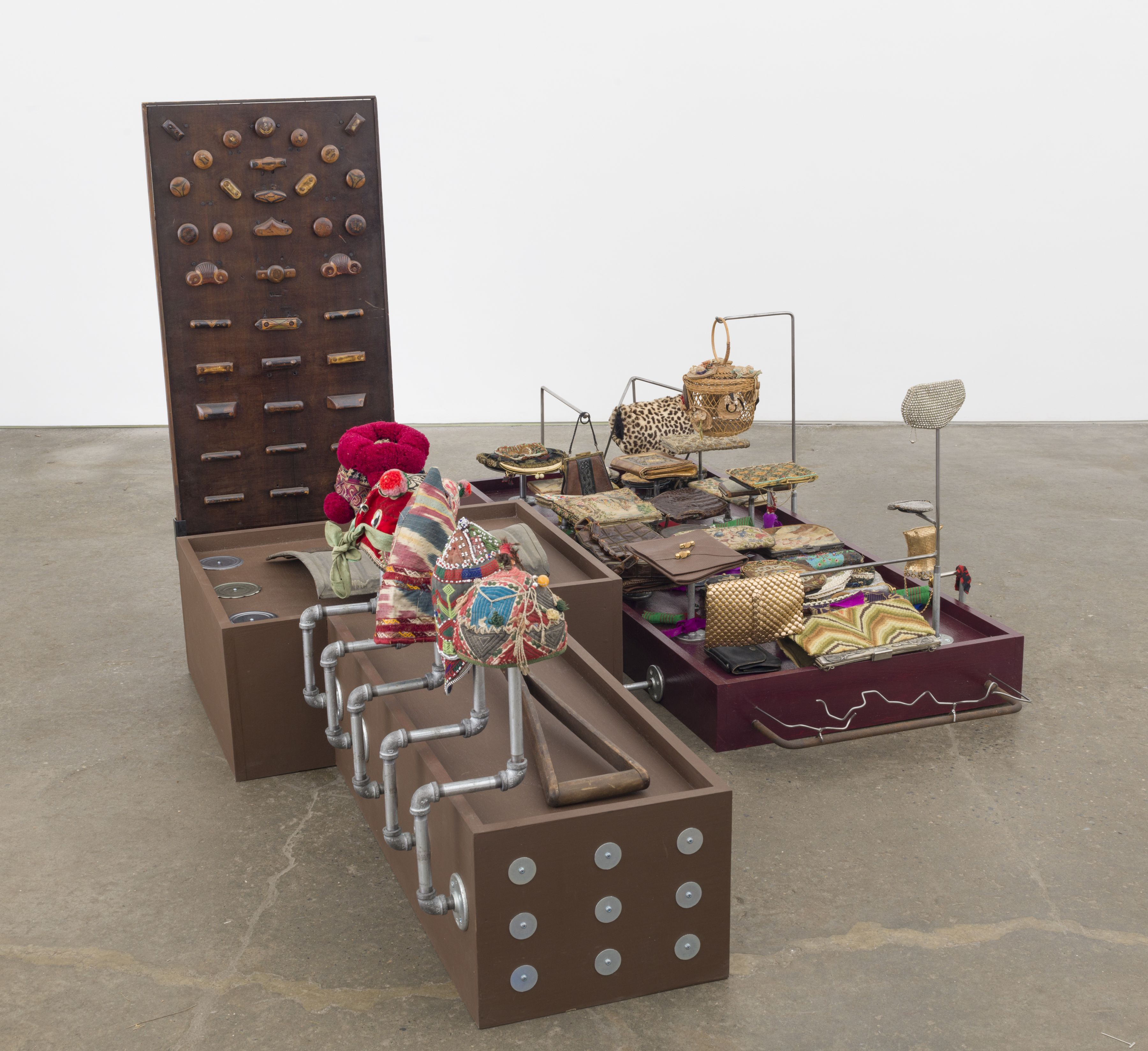 Collections - Love and work, 2017-18, collection of evening bags, handmade snow shovel, baby hats (China, Afghanistan, Uzbekistan), panel of drawer knobs, tin can covers, metal rods, plumbing parts, wooden platforms