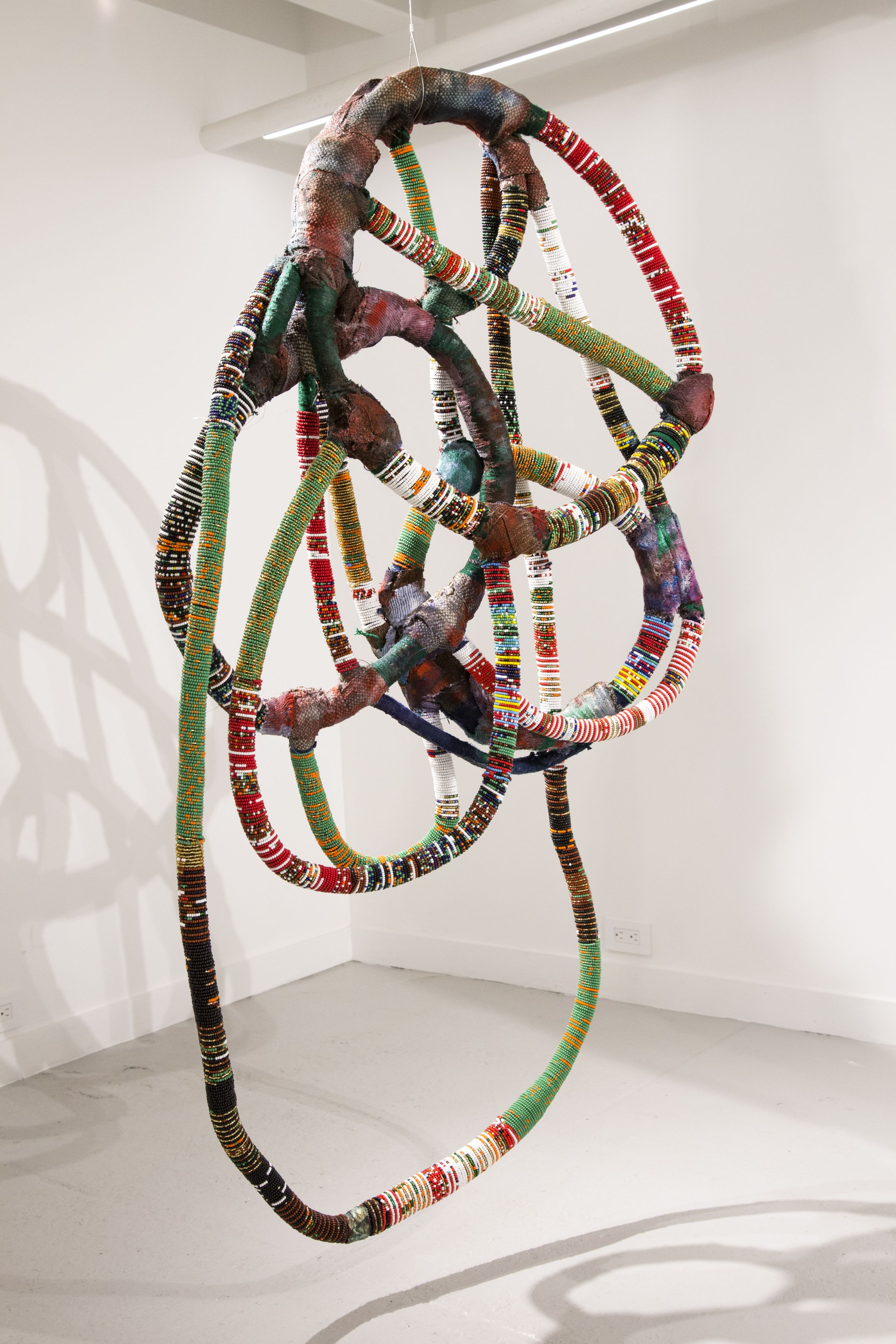 Leonardo Benzant  The Chameleon's Journey: Galveston, 2017  from the series Paraphemalia of the Urban Shaman M:5  clothes/fabric, string, monofilament, glass beads, gel medium, acrylic, vija (Ashiote), coffee grinds, powdered charcoal, glitter and miscellaneous  height: 70 inches