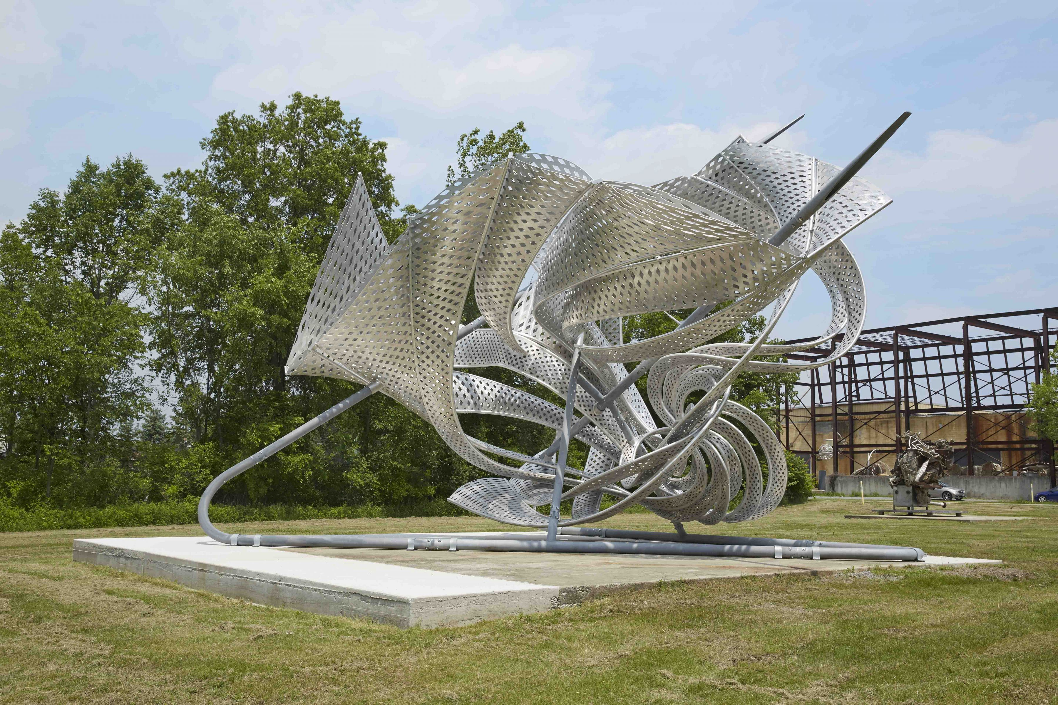 a twisted metal sculpture placed outside near frank stella's studio