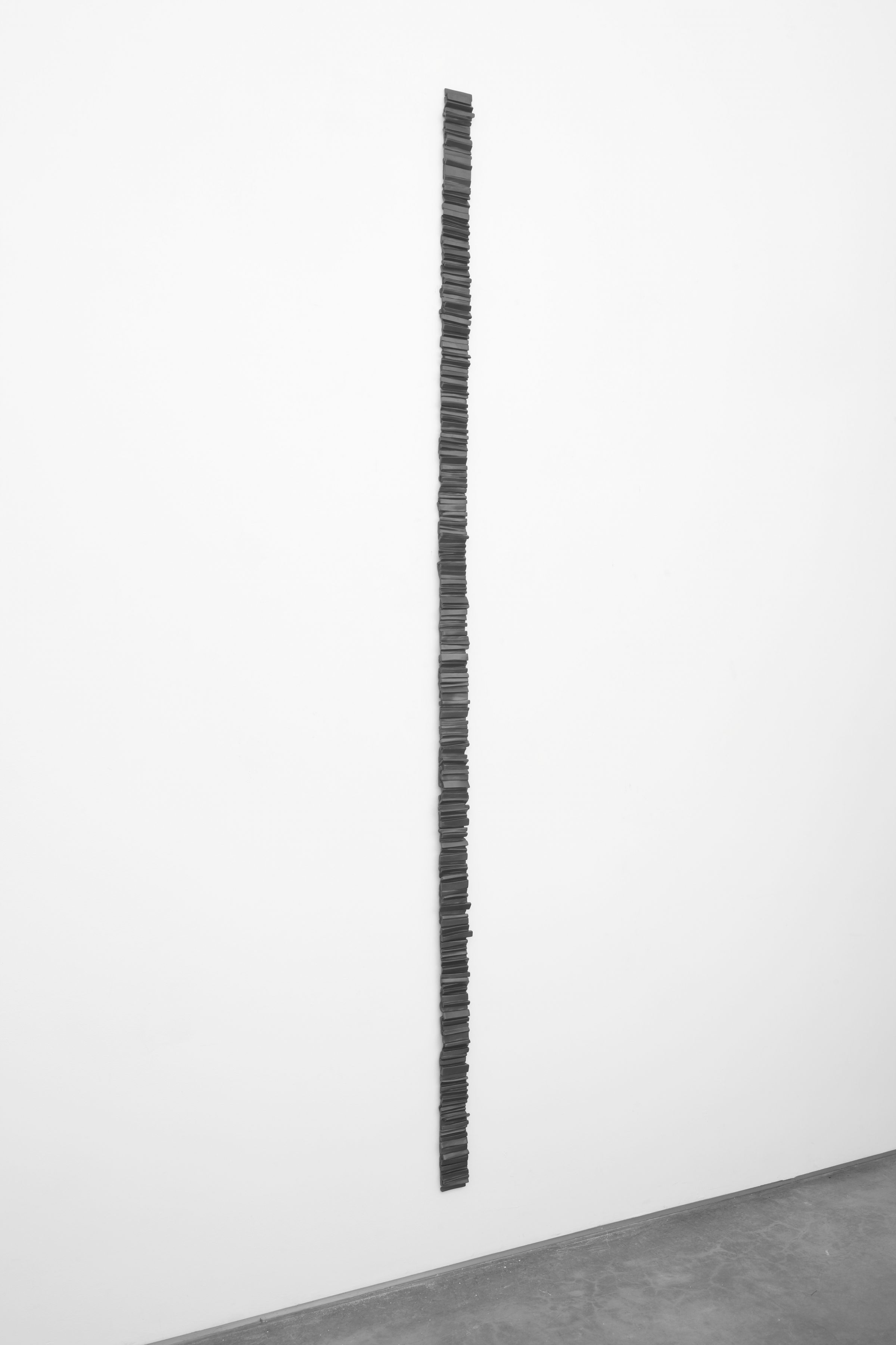 a bronze wall sculpture that is a vertical line up the wall by anthony pearson