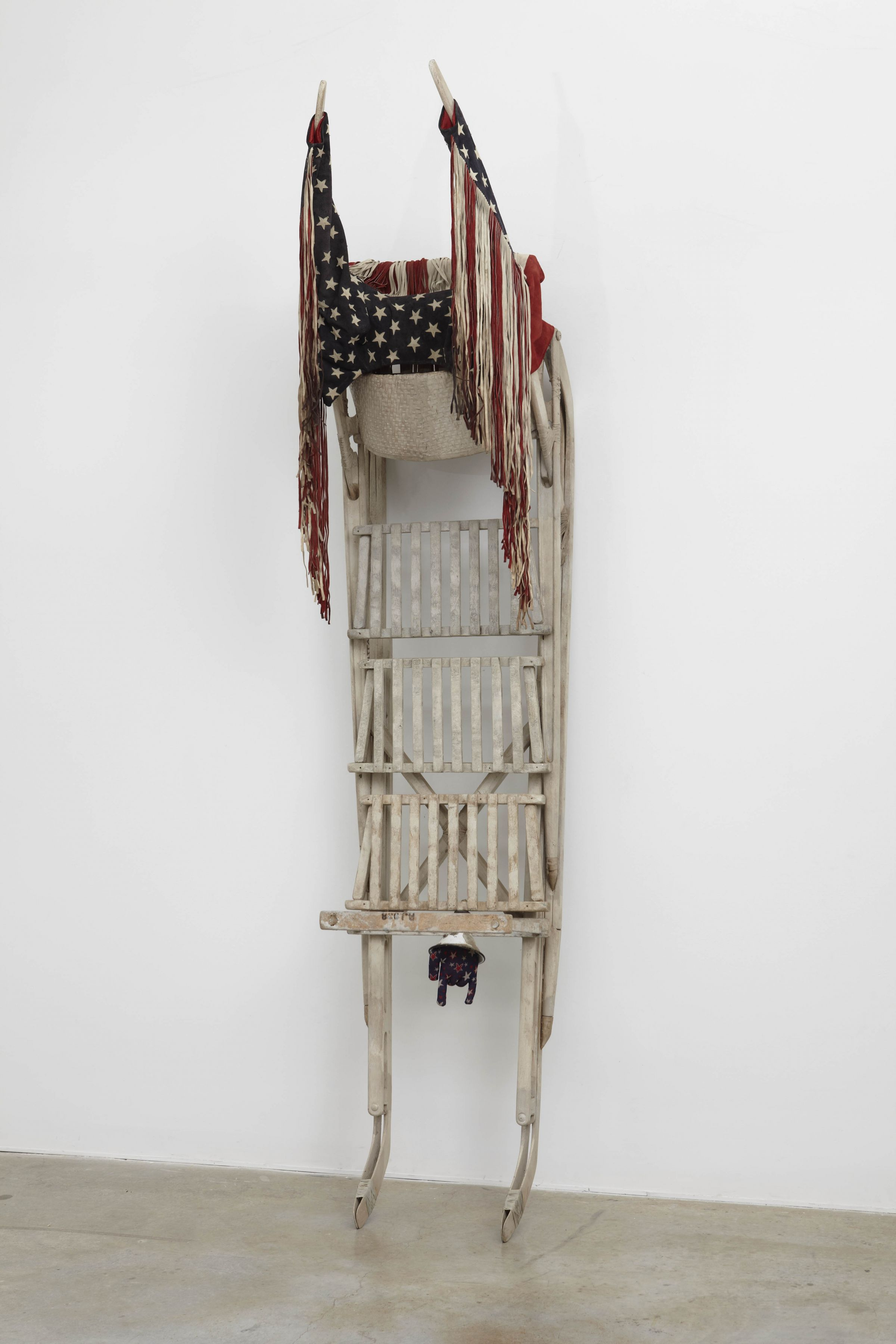 a sled with american flags by salvatore scarpitta on exhibition in a new york city gallery