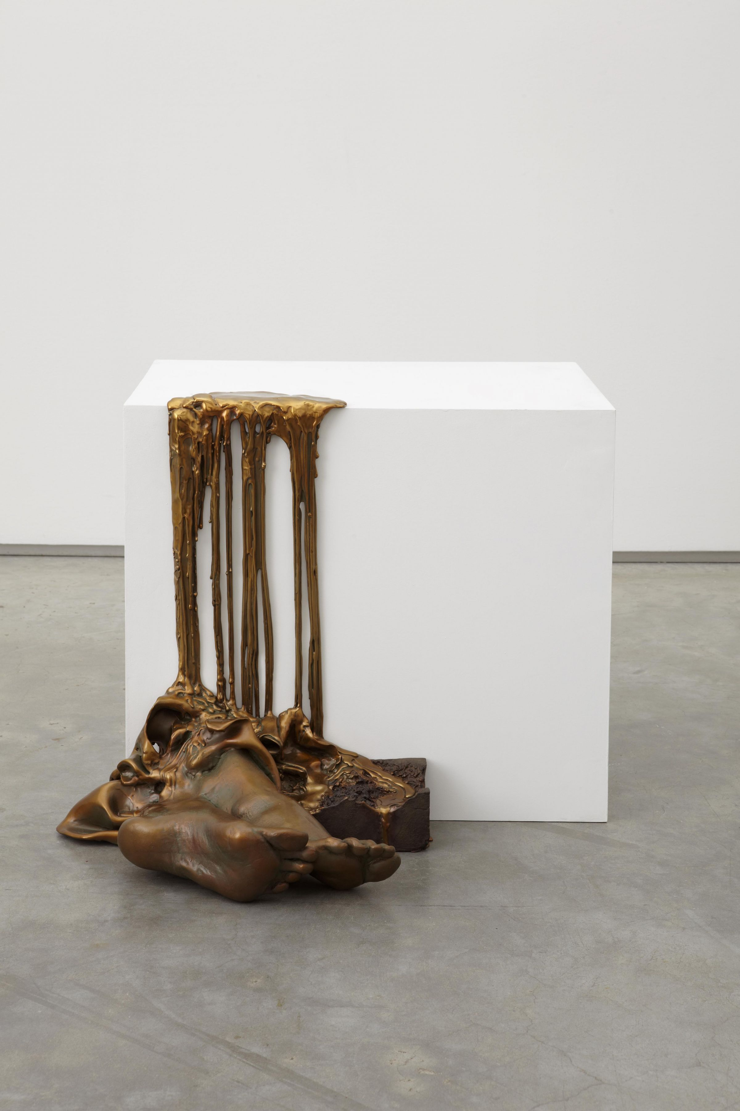 a bronze work of art that is dripping off a pedestal by Diana Al-Hadid