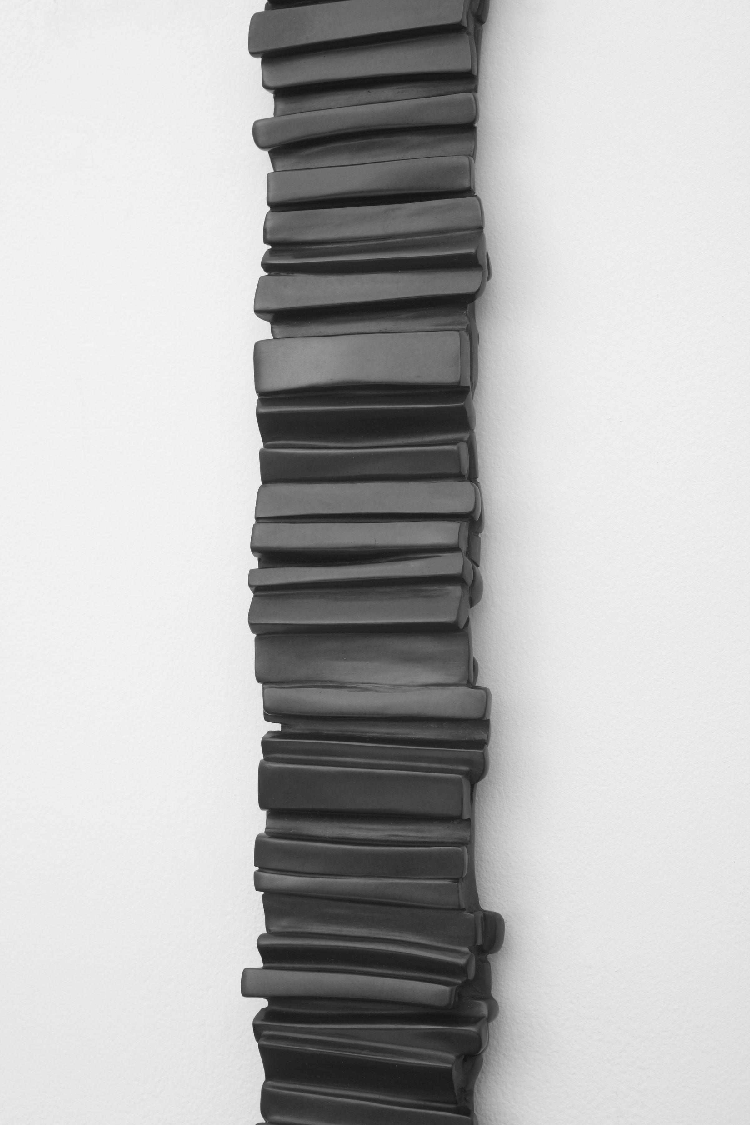 a detail of a vertical bronze wall hanging by anthony pearson composed of small stripes