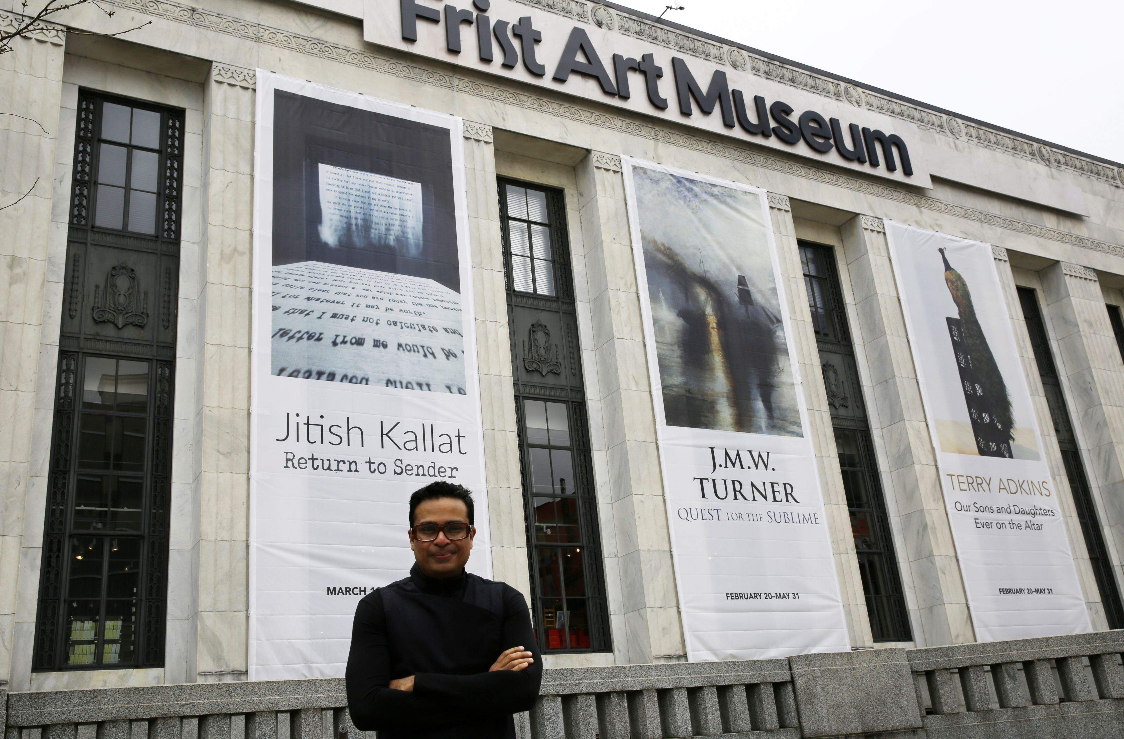 Photo of the artist standing in front of the Frist Art Museum where a banner with his name hangs on the facade