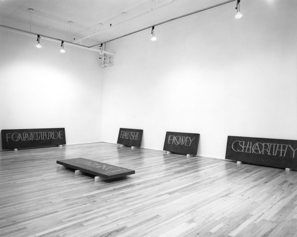 black and white installation view of five inscribed stone slabs place around a room