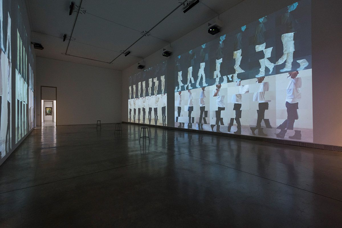 installation view of a darkened gallery with large-scale projections of two rows of a male figure stacked and segmented