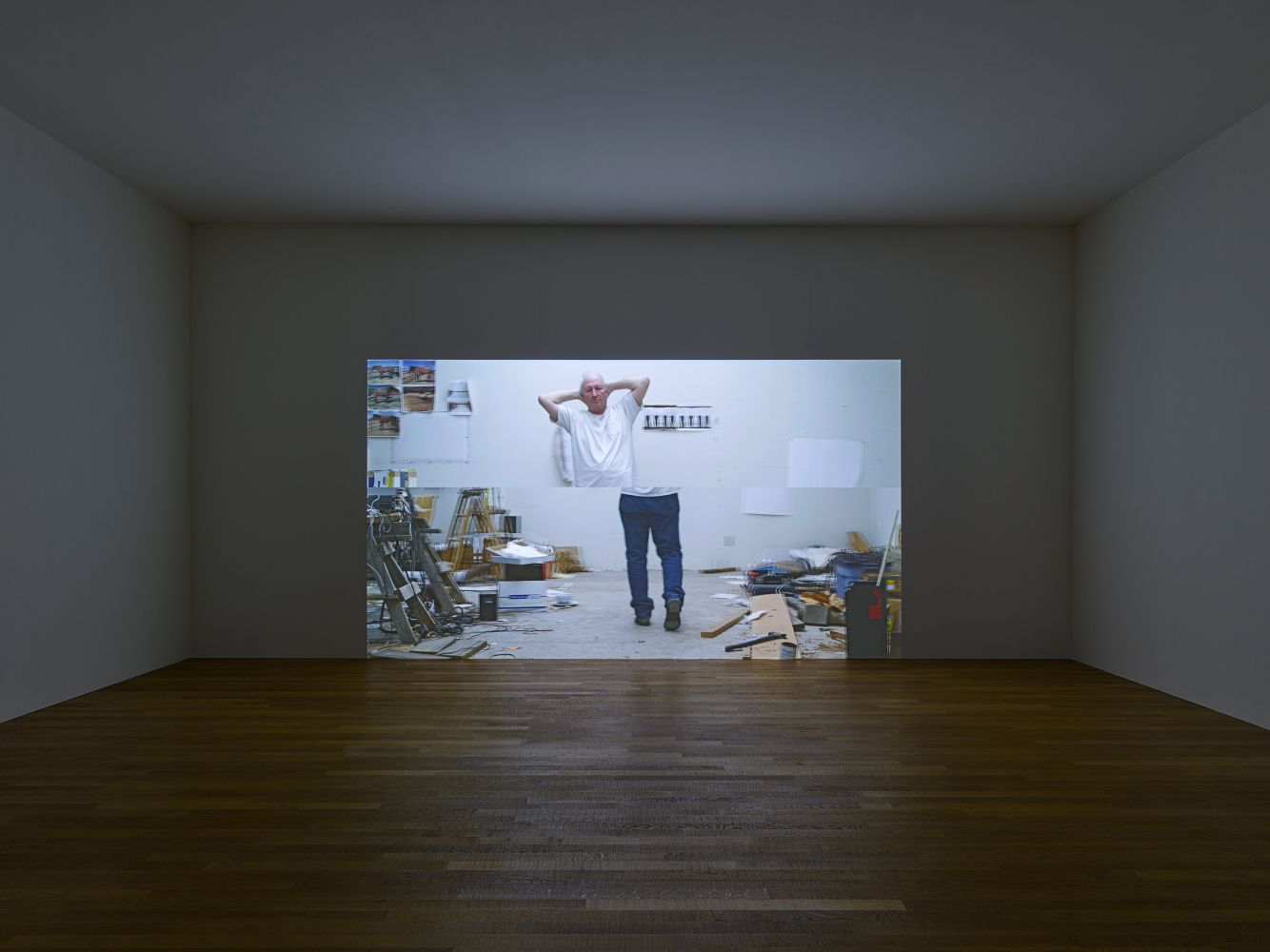 installation view of a darkened gallery with a projected image of a man walking with his hands behind his head in a contrapposto pose