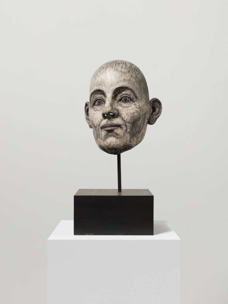 Resin, fiberglass, stone dust and acrylic sculpture of a head with dark features