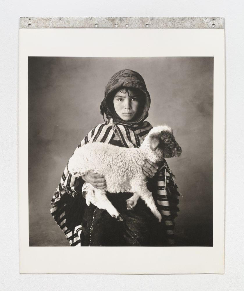 Black and white photographic portrait of a child holding a lamb.