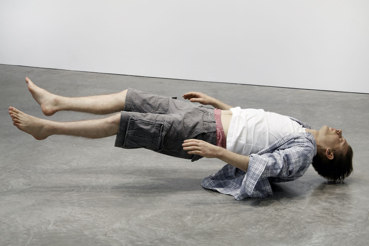 Installation view of a silicone, steel, hair, urethane and clothing sculpture by Tony Matelli featuring a hyper-realistic man levitating