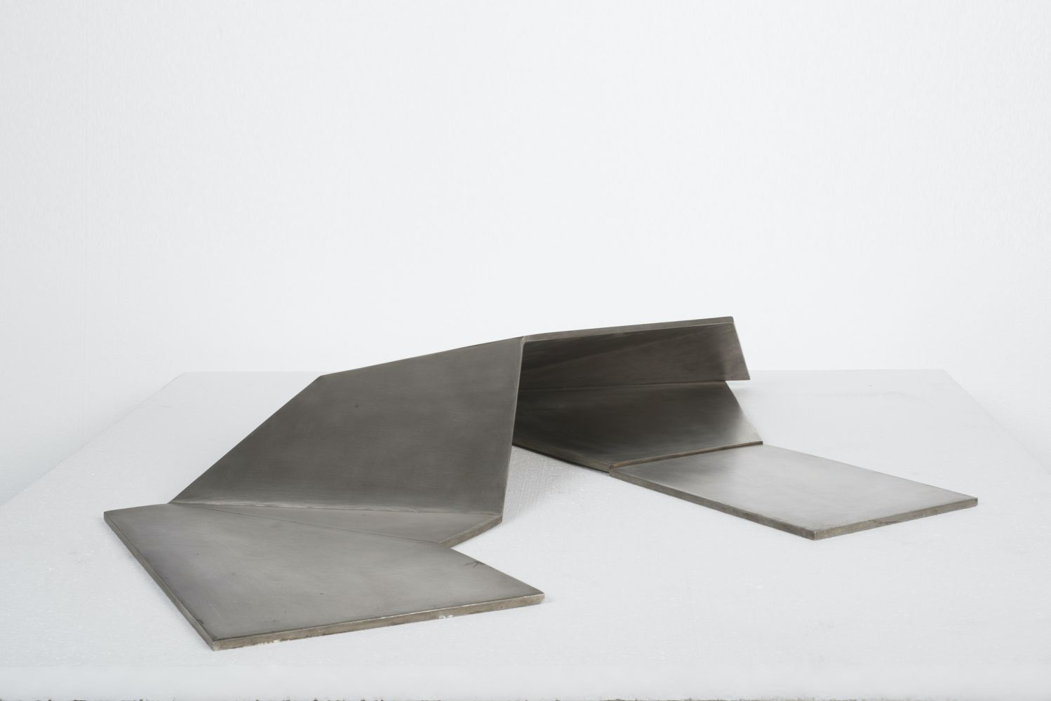 Angular, reflective, and sharp stainless steel sculpture with slate grey hues by Beverley Pepper.
