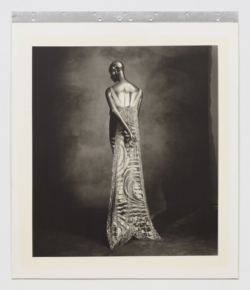 Black and white photographic portrait of the back of a woman's ornate dress.