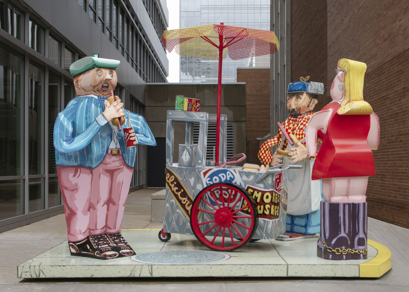 An installation shot of Red Grooms' sculpture depicting a hot dog vendor and two customers using exaggerated perspective.