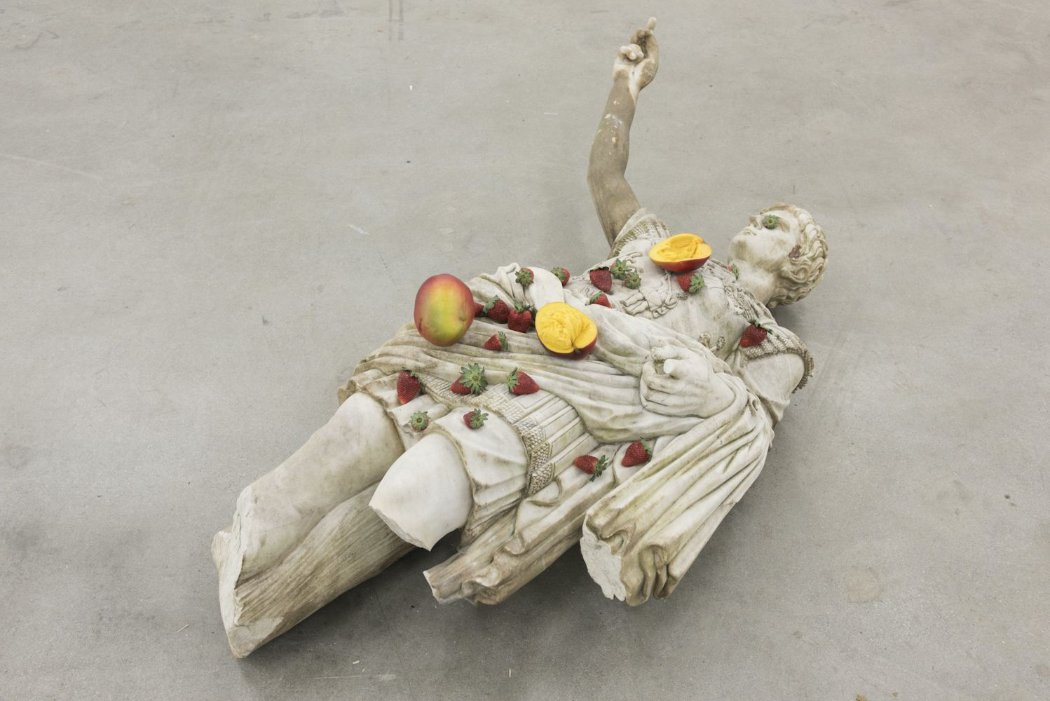 Hyper realistic sculpture by Tony Matelli of a sculpture of Julius Caesar on the ground with strawberries and sliced mangoes spread throughout