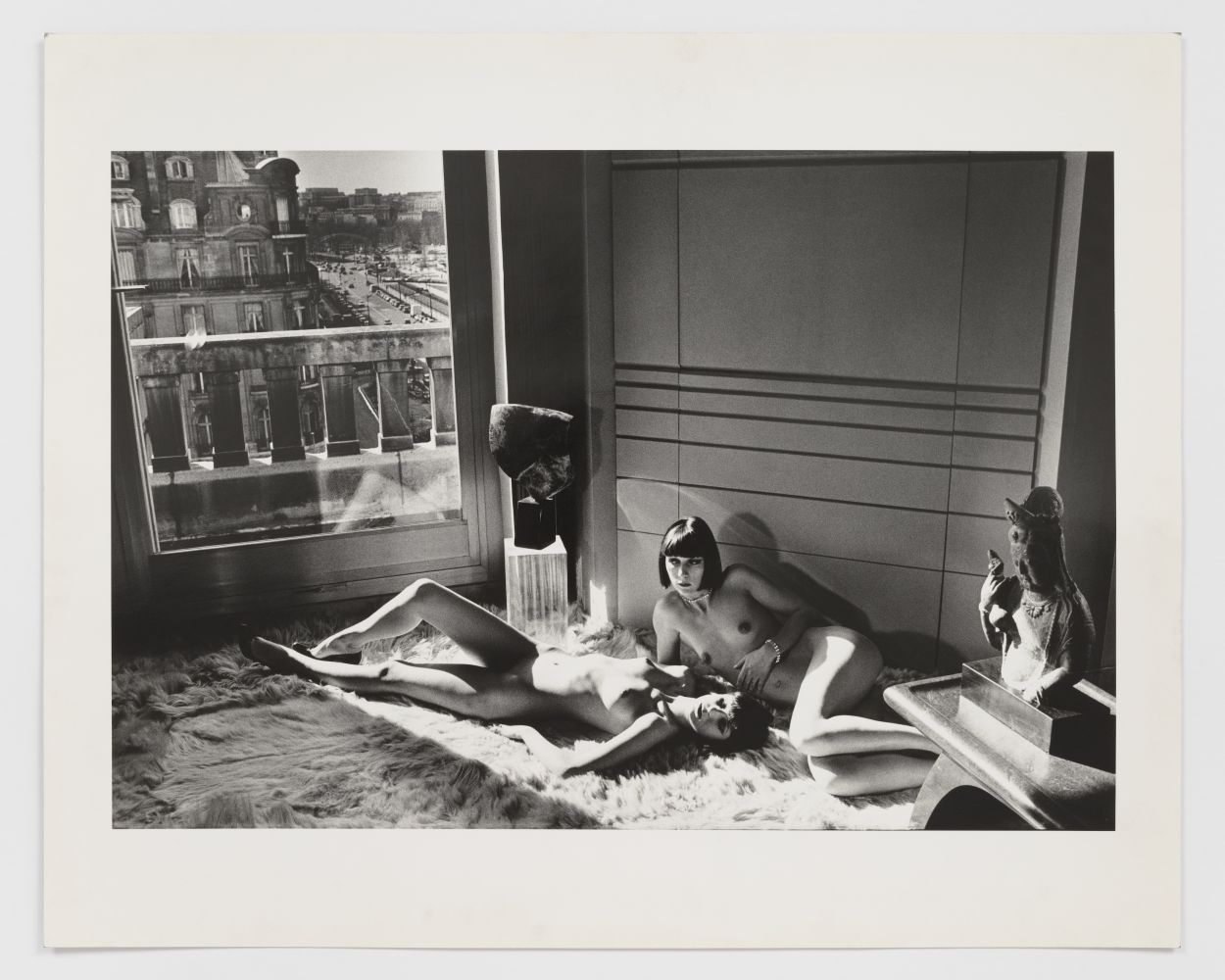 Black and white photographic print by Helmut Newton of two nude women laying down under a window