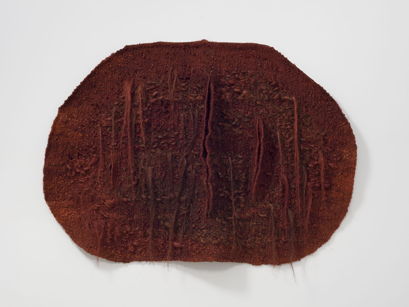 Horizontally oriented, oval shaped, red textile with slits by Magdalena Abakanowicz