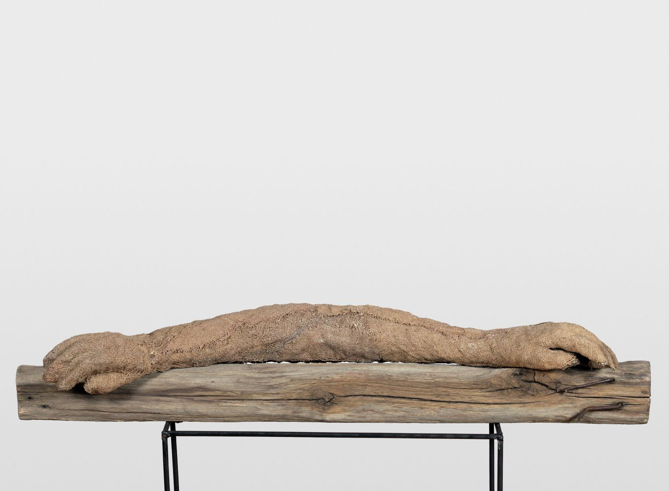 Horizontal burlap, wood and steel sculpture by Magdalena Abakanowicz of two arms joined at the elbow