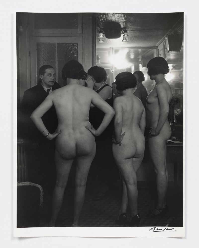 Black and white photographic portrait of three nude women standing before a man at Suzy's.