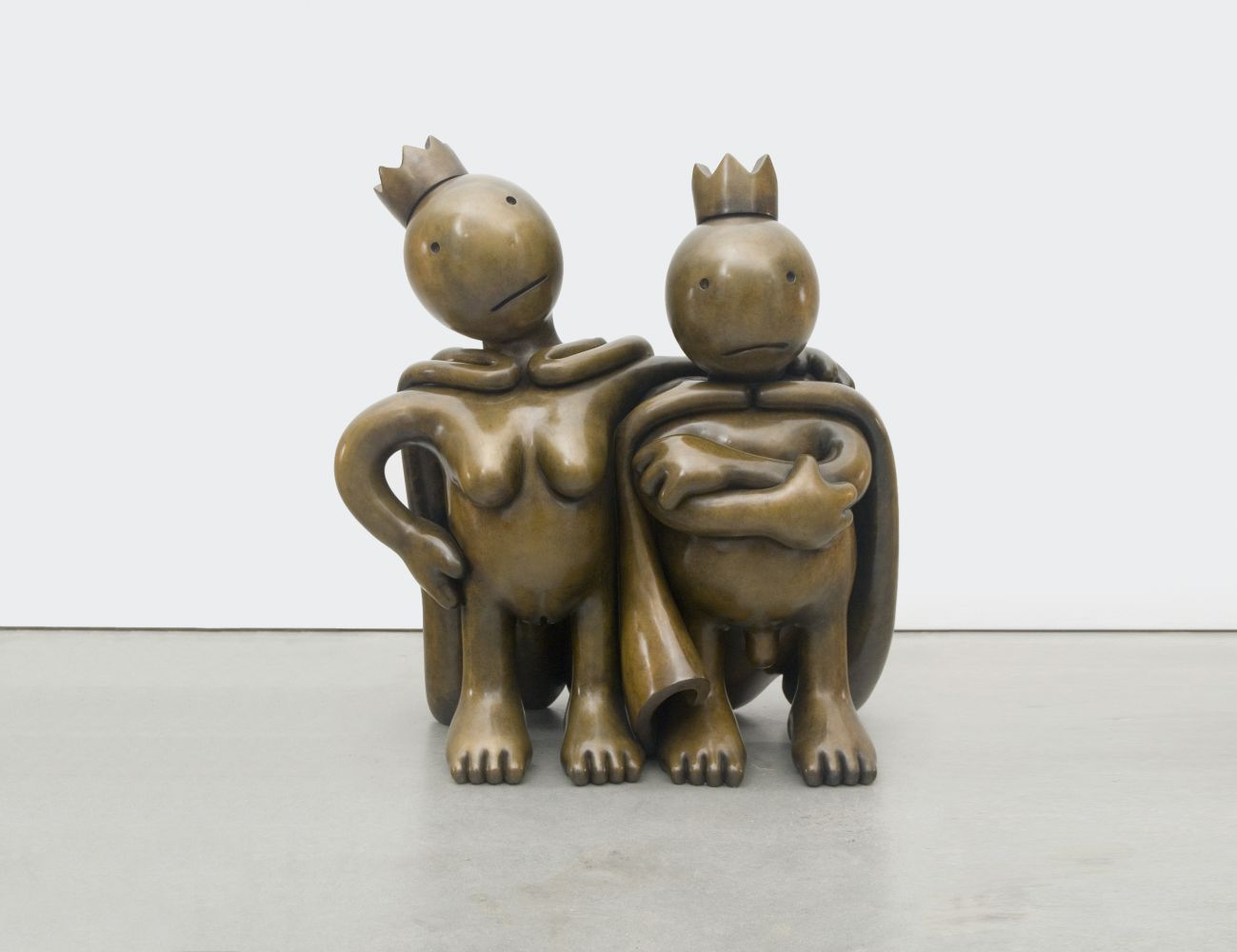 Two nude bronze figures with capes and crowns by Tom Otterness.