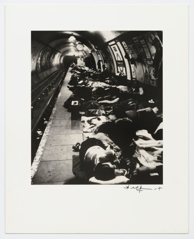 Black and white silver gelatin print of people sheltering in the underground train station (The Tube).