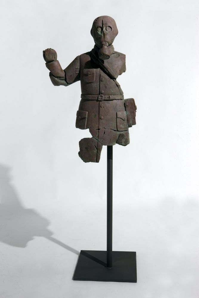Rusted and fragmented bronze statue of a man in a gas mask.
