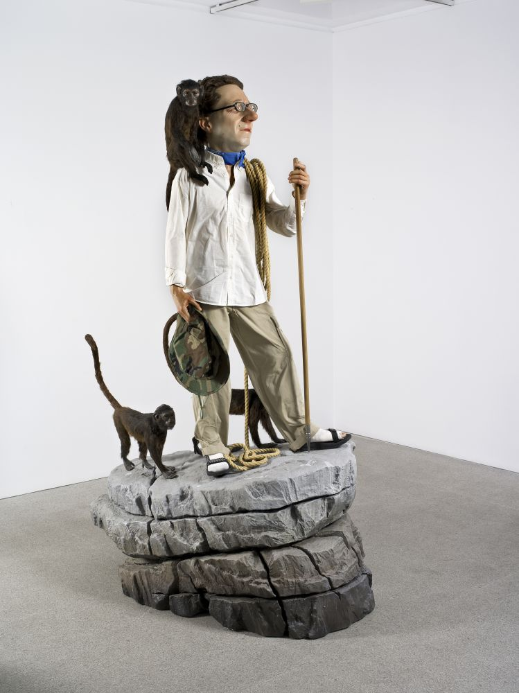 Installation shot of a life-size and hyper-realistic sculpture of an explorer standing on a rock surrounded by monkeys