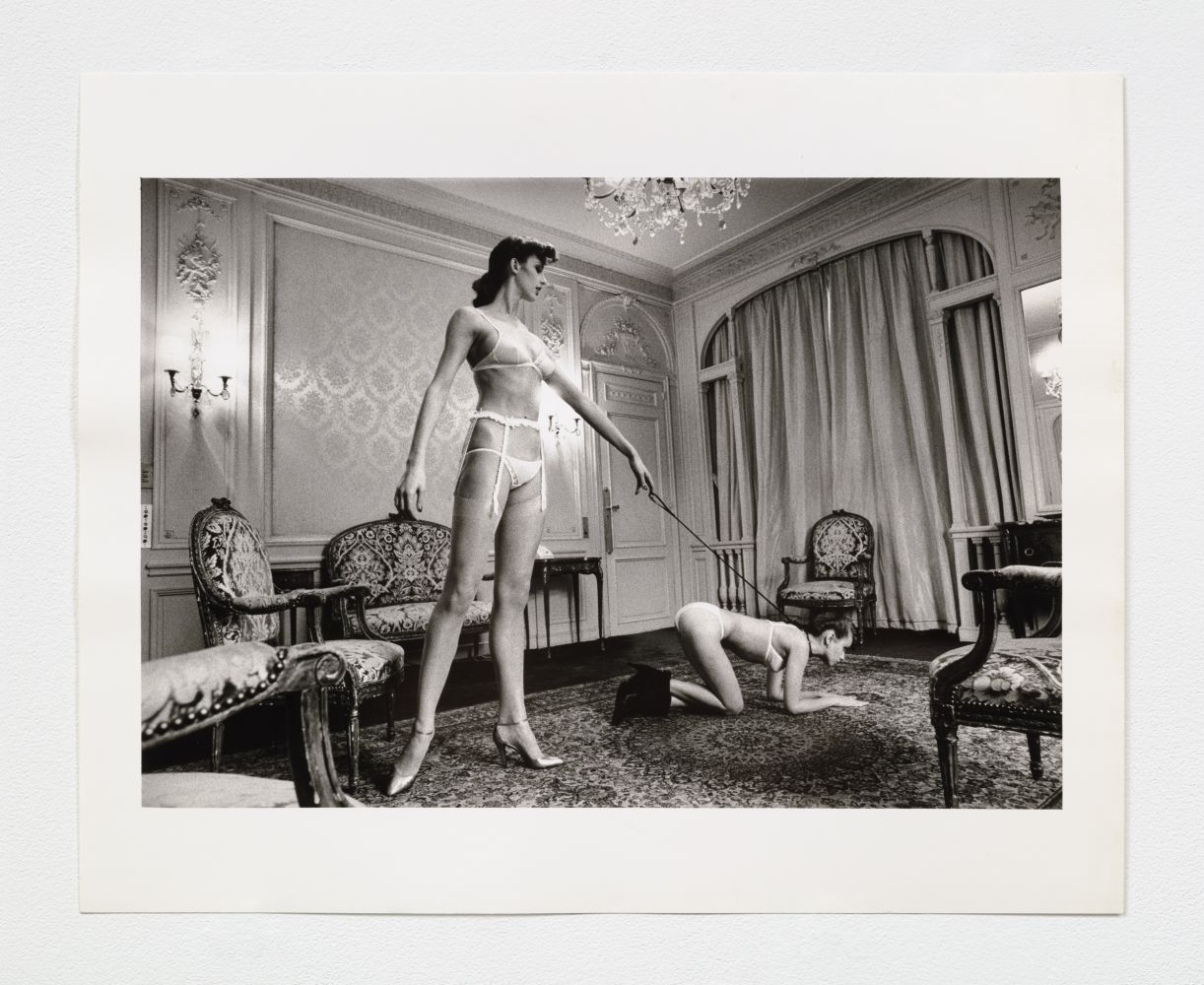 Black and white photographic print of a standing woman holding a leash attached to a crawling woman