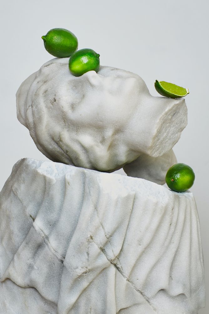 Detail photograph of a sculpture by Tony Matelli featuring the head of the goddess Diana and surrounded by limes