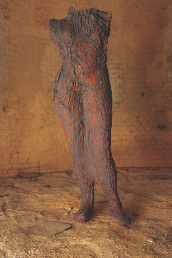 Textured earthenware sculpture of human body with burnt orange hues by Michele Oka Doner.