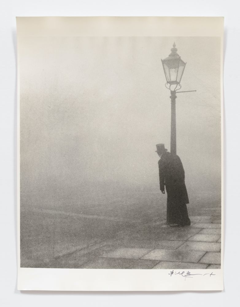 Black and white silver gelatin print of man leaning on lamp post in fog.