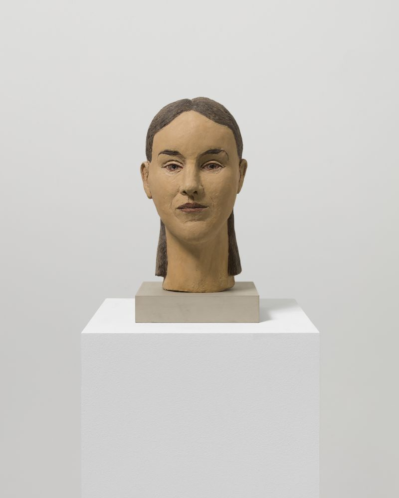 Painted fiberglass sculpture of a woman's head with brown hair and eyes