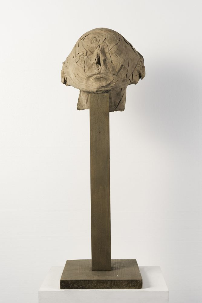 Cotton, resin, and sand sculpture of a head on a pedestal