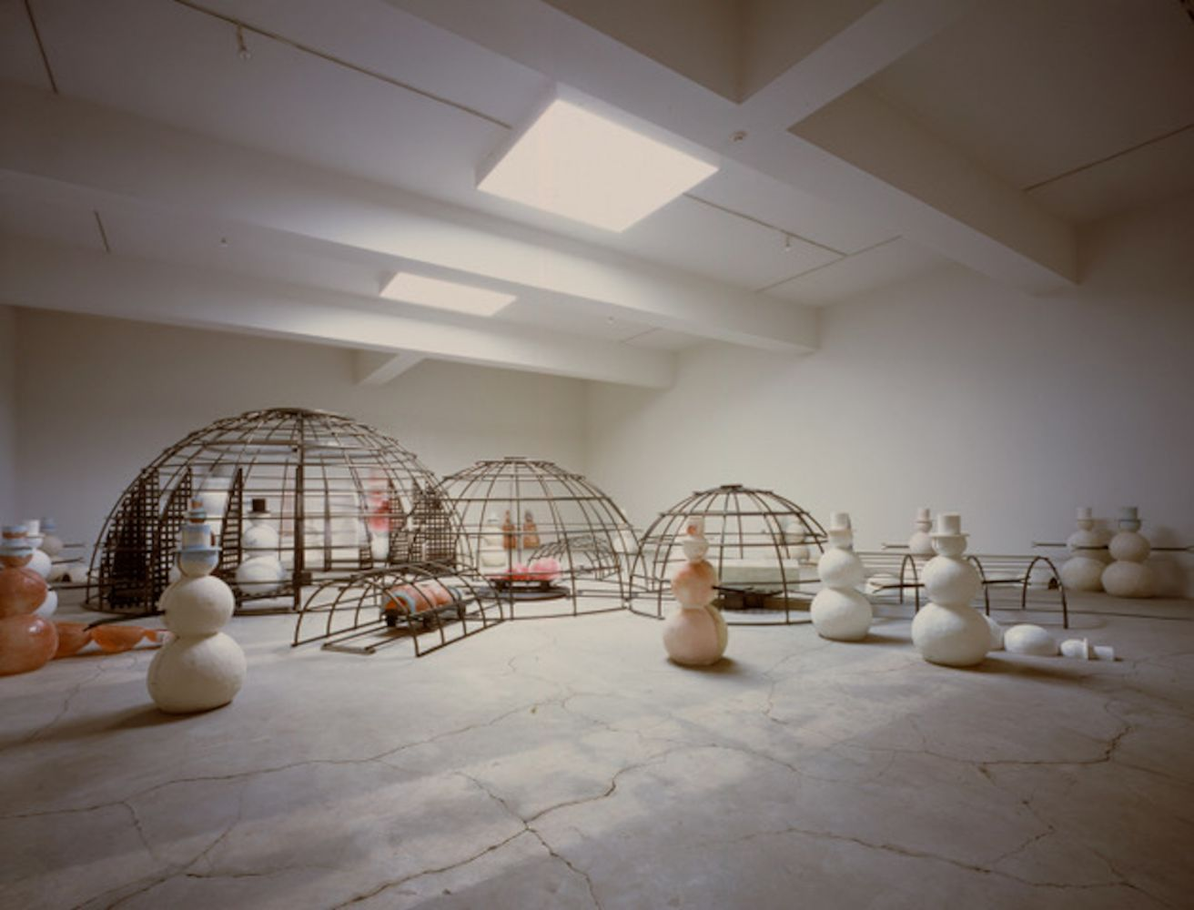 Installation shot of Dennis Oppenheim's cluster of white and pink snowmen alongside caged steel igloos.