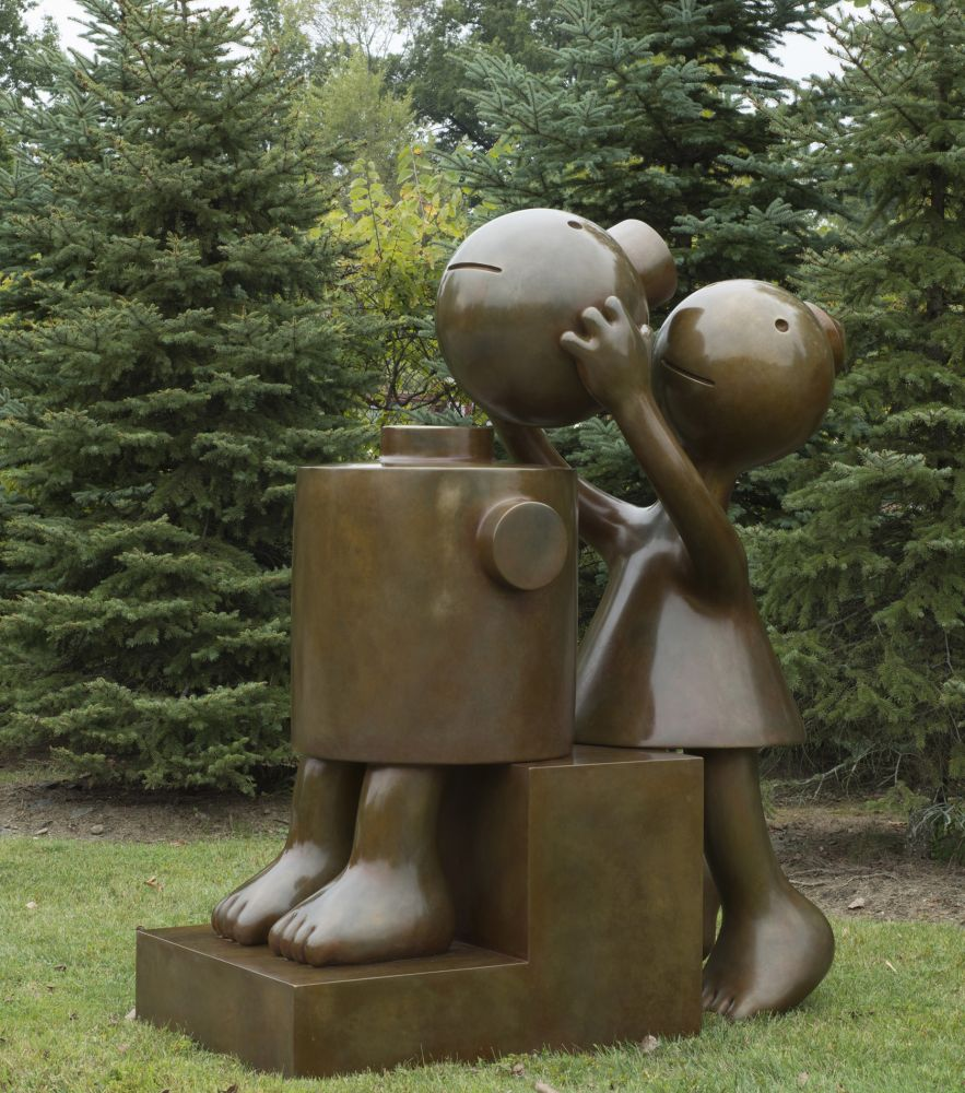 Installation shot of Tom Otterness' sculpture of a dressed figure placing a head atop another seated figure.