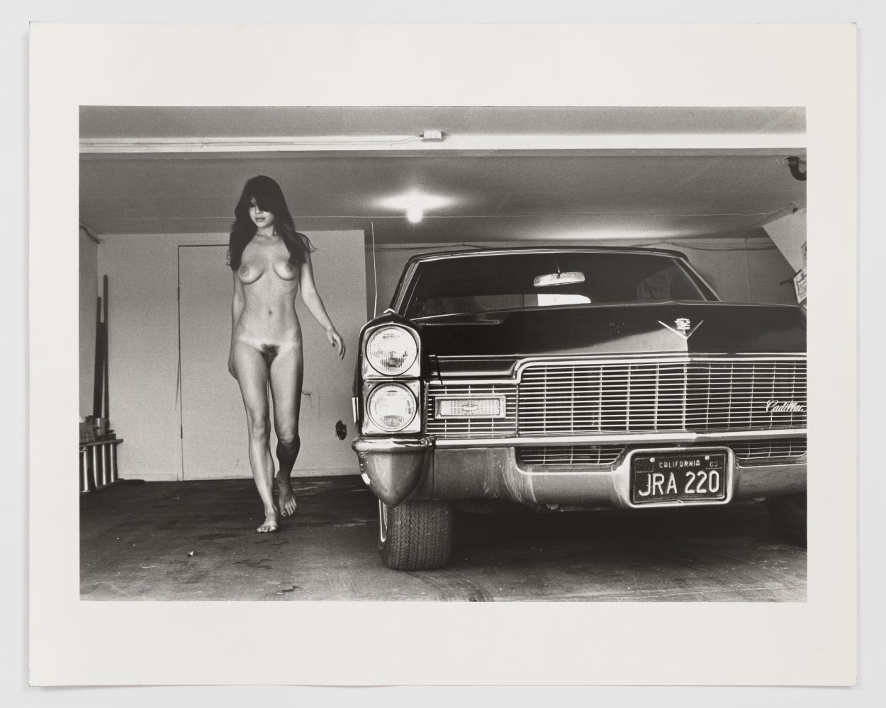 Black and white photographic print of a nude woman standing beside a car
