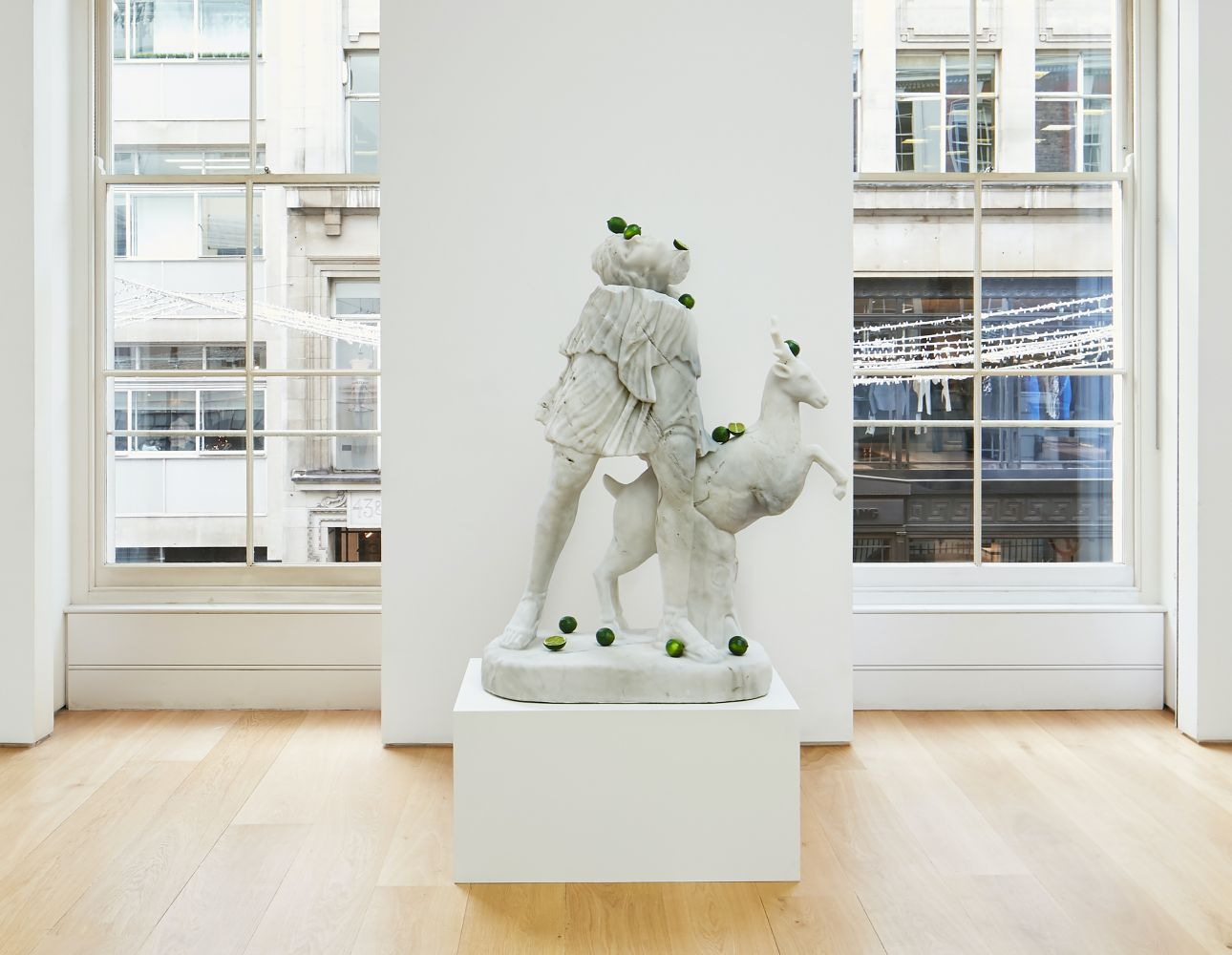 Installation view of a painted bronze, cast glass, marble sculpture featuring the mythical goddess Diana and a deer with sliced limes spread throughout