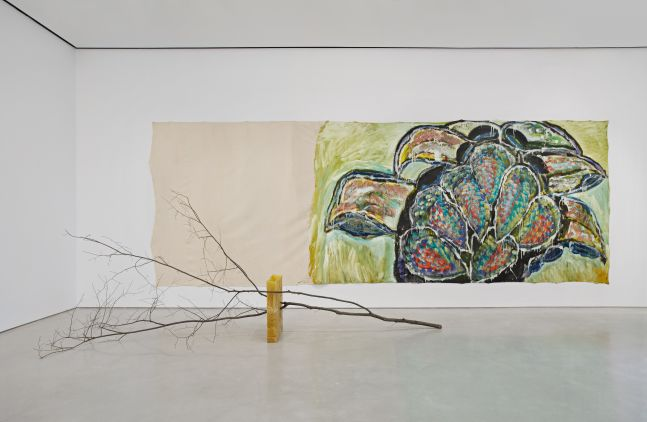 a large branch on its side supported by a wax block while a large-scale painting of foliage hangs on the wall behind it