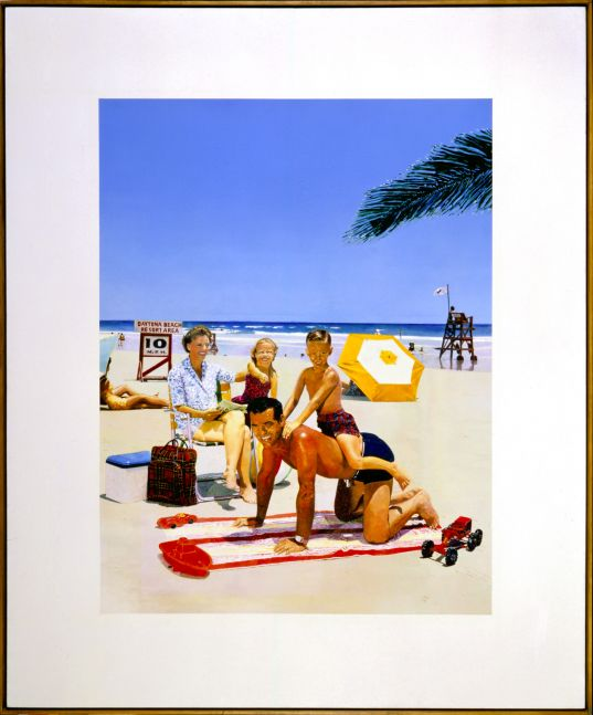 sunny beach scene of a family of four where the son rides the father's back and the wife and daughter sit behind them