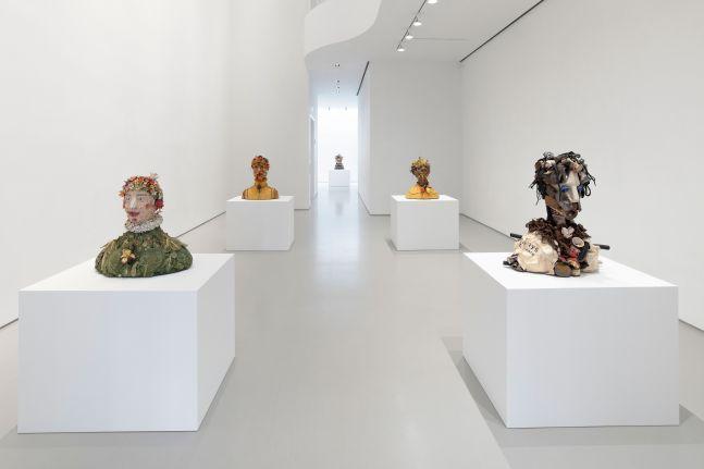 five bust sculptures installed in gallery on white pedestals