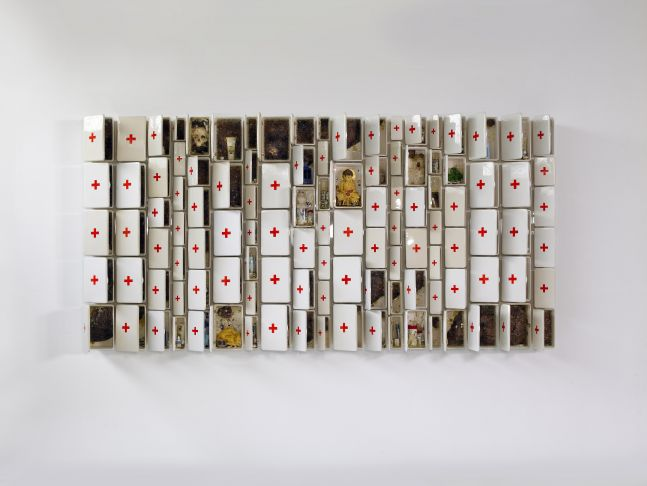 a large ceramic sculpture composed of first aid boxes of varying sizes filled with ceramic objects including a Buddha, honeycomb and pill bottles