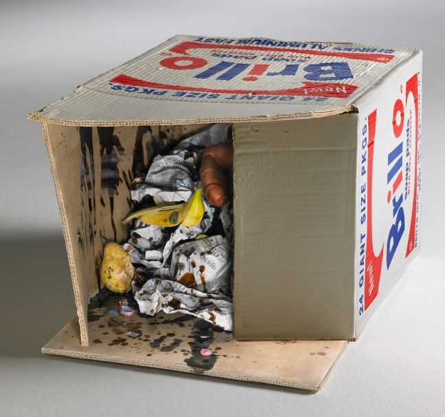 ceramic brillo box on its site and open to reveal fruit, balled up newspapers and a dildo
