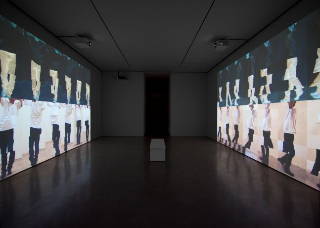 installation view of a darkened gallery with projections on opposite walls showing stacked rows of segmented man