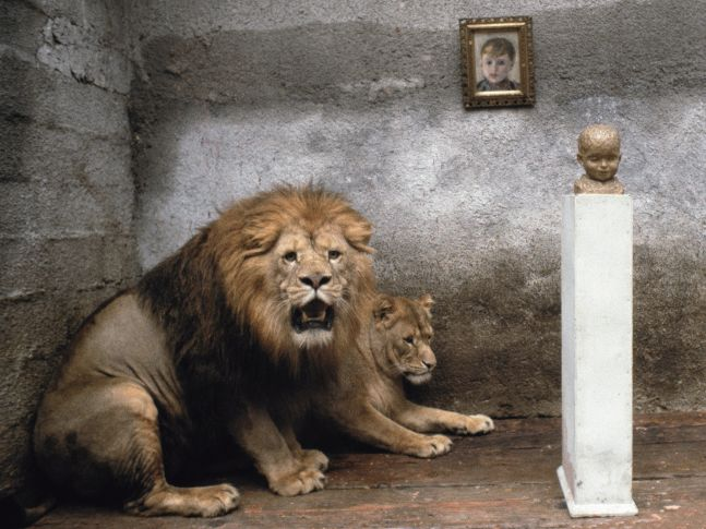 male and female lions next to a pedestal holding the bust of a child in a cement room