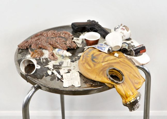 stainless steel and ceramic table holding an octopus, spilled espresso cups, a gun, batteries and a gas mask