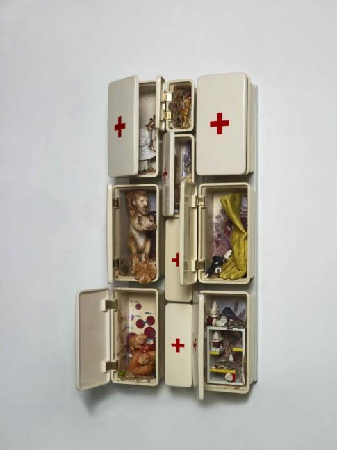 ceramic sculpture composed of first aid boxes of varying sizes filled with ceramic objects including a rubber glove, a bust of a man and other objects